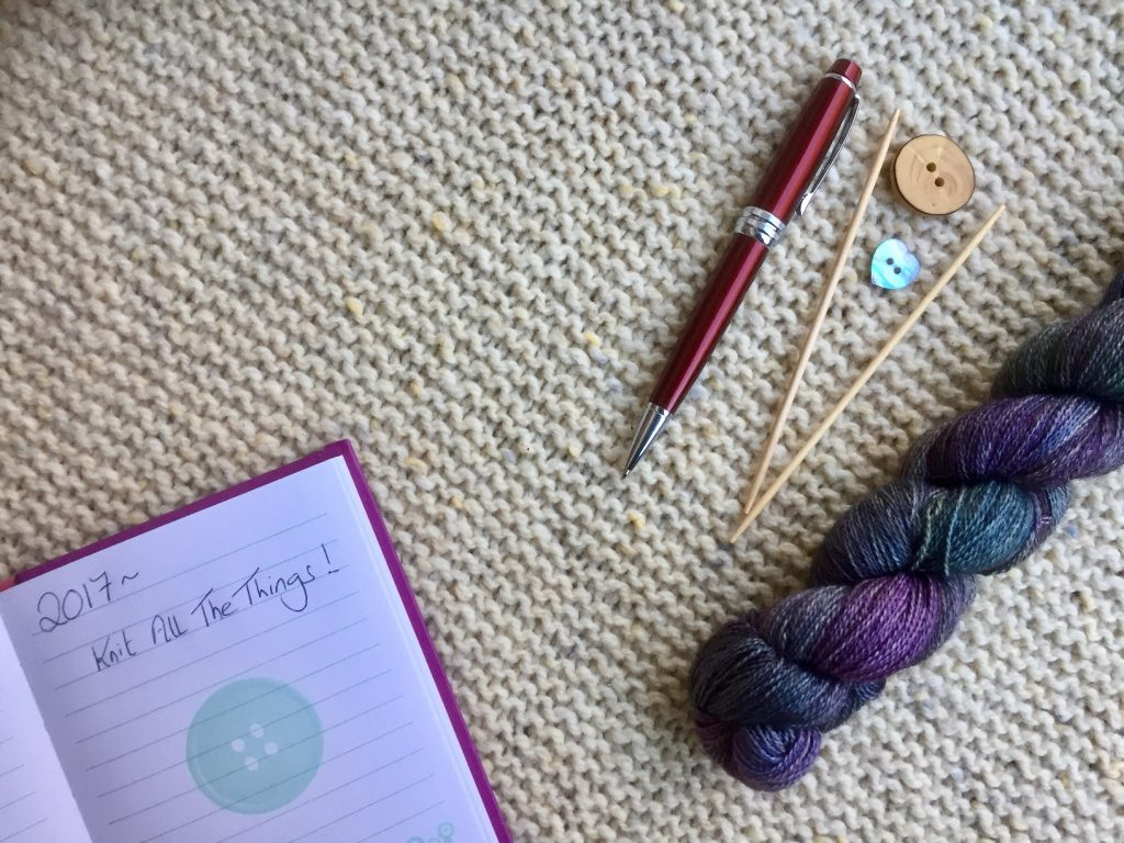 """Flat lay with notebook, pen, needles and malabrigo yarn. Notebook features the text """"2017 - Knit All The Things"""". Plans for This is Knit 2017. Featured events."""