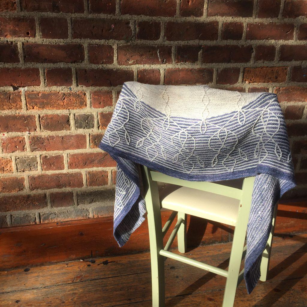 The Cypri Shawl by Amanda Scheuzgerin Hedgehog Fibres Sock Yarn. Draped over a chair.
