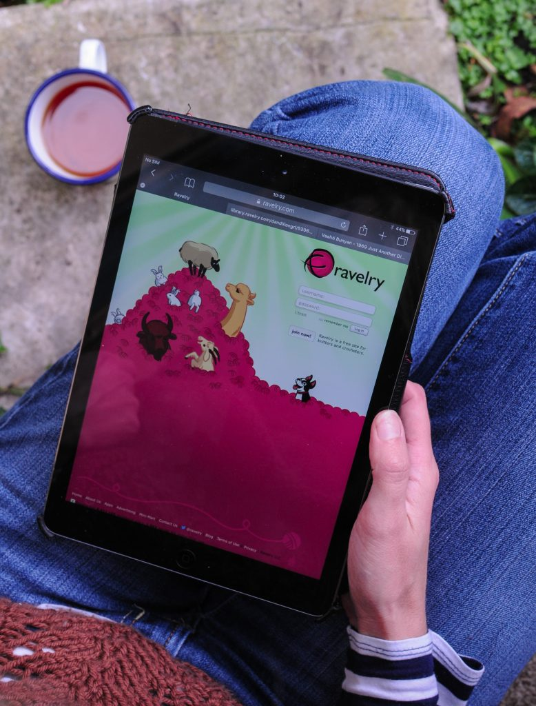 A knitter holding an iPad with Ravelry home page on the screen with a cup of tea in the background. Image by Kate from A Playful Day