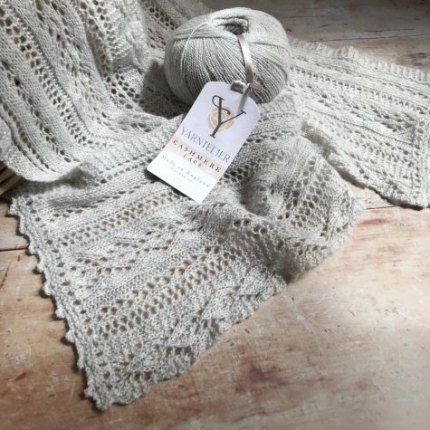 Lace scarf draped over wood table with ball of cashmere lace sitting on top