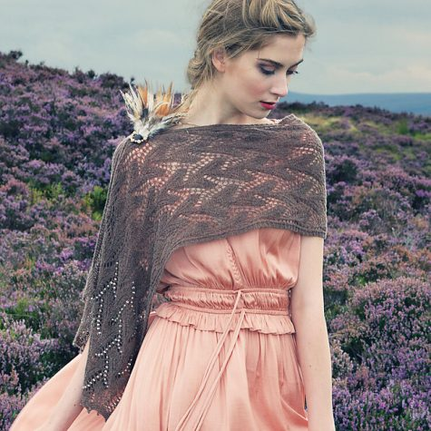Woman in pink dress in field of purple flowers wearing a beige lacey wrap over her shoulders looking down
